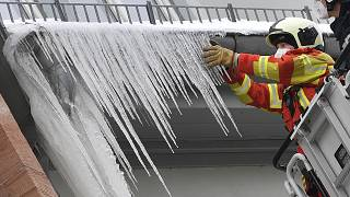 Firefighters break large icicles from the gutter of a house in the city centre of Erfurt, Germany, Thursday, Feb.11, 2021.