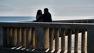عاشقان إيطاليان لم ينسهما الحب أنّهما في زمن كورونا إذ يرتدي كلٌ منهما كمامة تحميه من الفيروس