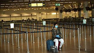 A passenger, wearing a face mask to protect against the spread of coronavirus, sits at the almost empty departures hall at the Zaventem international airport in Brussels,