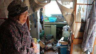 امرأة يابانية تقف في مطبخها المتناثر إثر الزلزال، فوكوشيما 14 فبراير 2021