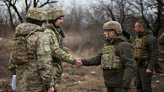 الرئيس الأوكراني فولوديمير زيلينسكي يصافح جنديًا أثناء زيارته لمنطقة دونيتسك التي دمرتها الحرب 11 فبراير 2021