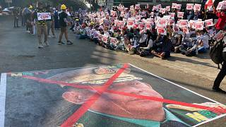 A large image that has an X mark on the face of Commander in chief Senior Gen. Min Aung Hlaing lies on a road as anti-coup protesters gather in Yangon, Sunday, Feb. 14, 2021.