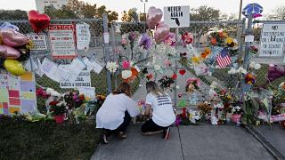 People light candles at a makeshift memorial outside a high school where 17 students and faculty were killed in a mass shooting in Parkland, Florida. Feb. 18, 2018