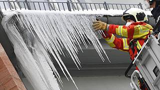 Feuerwehrleute brechen große Eiszapfen aus der Dachrinne eines Hauses in Erfurt, Deutschland, 11.02.2021
