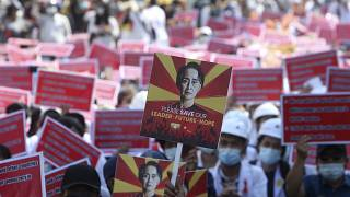 A protester holds up a placard with an image of deposed leader Aung San Suu Kyi during an anti-coup rally in front of the Mandalay railway station in Myanmar. Feb. 15, 2021.