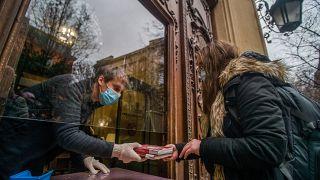 Egy könyvtáros szolgál ki egy nőt a Fővárosi Szabó Ervin Könyvtár cserepontján a VIII. kerületi Szabó Ervin téren 2021. február 10-én.