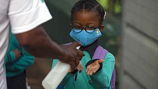 Une élève se désinfecte les mains avant de rentrer en classe pour la rentrée, le 15 février 2021, Johannesburg, Afrique du Sud