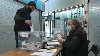 A masked voter places his ballot in a polling station in Barcelona, Catalonia, Spain