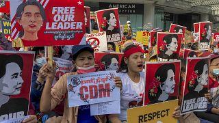 متظاهرون يرفعون صوراً لزعيمة ميانمار المحتجزة أونغ سان سو كي خلال احتجاج على الانقلاب العسكري في يانغون - ميانمار.
