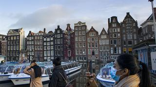 A woman, wearing a face mask to curb the spread of the COVID-19 virus, takes images of empty and moored canal cruise boats docked in Amsterdam, Netherlands, Thursday, Feb. 4,