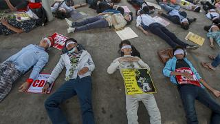 Demonstrators, with eyes blindfolded, lie down in the street to a protest a military coup in Yangon, Myanmar, Tuesday, Feb. 16, 2021.