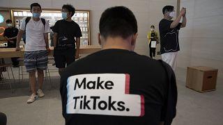 رجل يرتدي قميصاً يروج لـ تطبيق تيك توك في متجر آبل في بكين، الصين