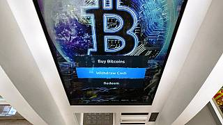 The Bitcoin logo appears on the display screen of a crypto currency ATM