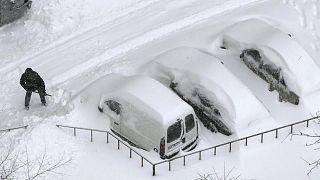 سائق يزيل الثلوج المكدسة حول سيارته في كييف ـ أوكرانيا