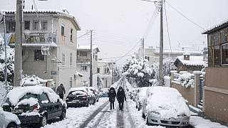 People walk in a street of Petralona neighborhood of Athens