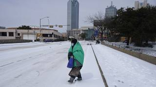 A woman wrapped in a blanket crosses the street near downtown Dallas, Tuesday, Feb. 16, 2021.