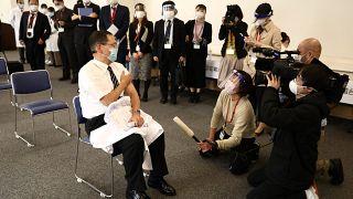 مدير مركز طوكيو الطبي كازوهيرو أراكي (يسار) يتحدث إلى وسائل الإعلام بعد تلقي جرعة من لقاح كورونا
