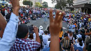 Demonstrators flash the three-fingered salute during a protest against the military coup in Yangon, Myanmar Wednesday, Feb. 17, 2021