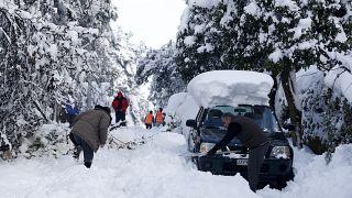 Los residentes tratan de limpiar una calle  después de una fuerte nevada en el suburbio de Dionysos, al norte de Atenas, el  17 de febrero de 2021.