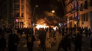 People gather next to a burning barricade during clashes after a protest condemning the arrest of rap singer Pablo Hasél in Barcelona, Spain, Wednesday, Feb. 17, 2021.