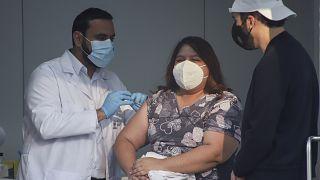 El ministro de Salud de El Salvador, Francisco Alabi, procede a vacunar a una enfermera ante la mirada atenta del presidente, Nayib Bukele.