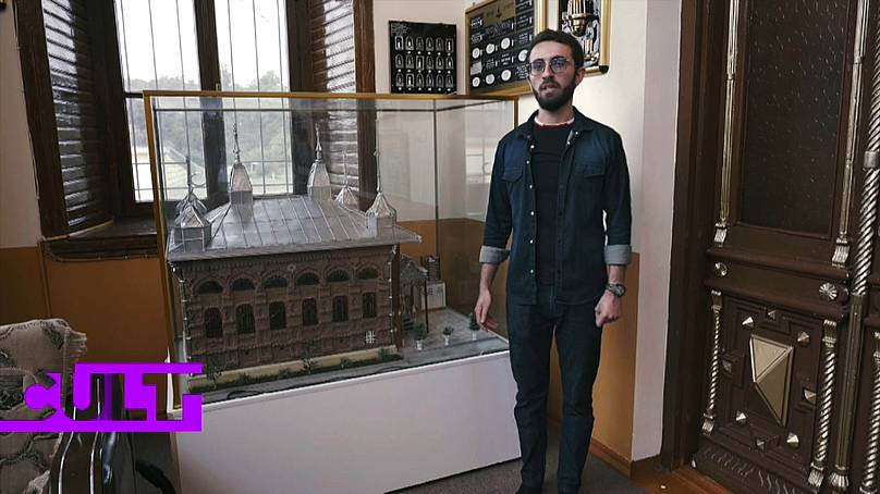 The museum guide next to a model of the six-domed synagogue