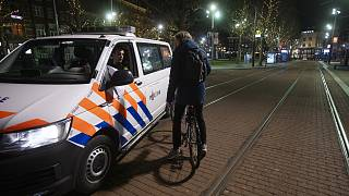 Dutch police check the papers of a man and his reason for breaking curfew in the otherwise deserted Rembrandt Square in the centre of Amsterdam, Saturday, Jan. 23, 2021.