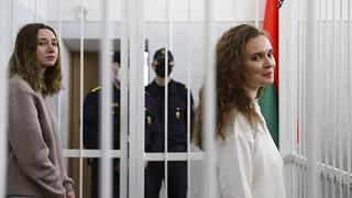 Journalists Katsiaryna Andreyeva, right, and Daria Chultsova stand inside a defendants' cage in a court room in Minsk, Belarus, Thursday, Feb. 18, 2021.