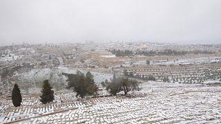 الثلج يغطي جبل الزيتون مع منظر مطل على قبة الصخرة في المسجد الأقضى في القدس. 2021/02/18