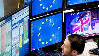 A computer screen shows news about the Brexit as a broker watches his screens at the stock market in Frankfurt, Germany, Wednesday, Jan. 16, 2019.