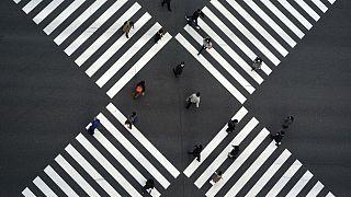 Japonya'nın başkenti Tokyo'da sosyal mesafe kurallarına uyarak karşıdan karşıya geçen insanlar.