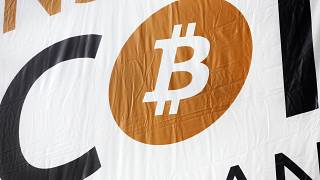 FILE: a bitcoin logo is displayed at the Inside Bitcoins conference and trade show, April 7, 2014 in New York.