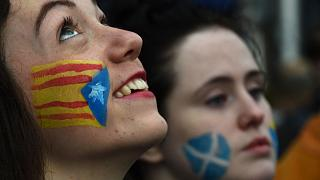 Demonstrators with the Catalan Estelada flag (left) and the Saltire painted on their faces during a protest to show solidarity with Catalonia in central Glasgow.