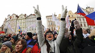 A woman flashes victory signs during a protest joined by thousands against the government restrictive measures to curb the spread of COVID-19 infections.