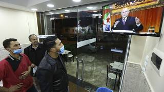 People in a restaurant watch President Abdelmadjid Tebboune's address on Thursday night