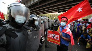 An anti-coup protester holds a poster as he stands in front of riot police in Yangon, Myanmar on Friday