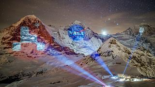 A giant projection of the NASA logos on the Bernese Alps mountains by Swiss light artist Gerry Hofstetter. Mannlichen, Switzerland. February 14, 2021