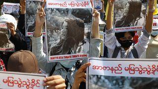 Manifestantes empunhando a fotografia de Mya Thwet Thwet Khine, baleada na cabeça