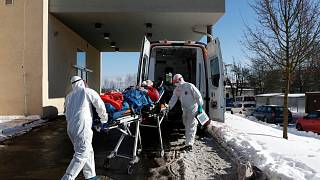 Medical workers move a covid-19 patient into an ambulance at a hospital overrun by the covid pandemic in Cheb, Czech Republic on Feb. 12, 2021.