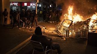 A man sits on a chair in front of a burning barricade during a protest condemning the arrest of rap singer Pablo Hasél in Barcelona, Spain, Friday, Feb. 19, 2021.