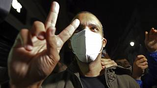 Algerian journalist Khaled Drareni flashes the V sign after being released from prison in Algiers, Friday, Feb.19, 2021.