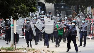 Police charge forward to disperse protesters in Mandalay, Myanmar on Saturday, Feb. 20