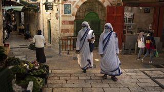Maszkot viselő katolikus apácák sétálnak a jeruzsálemi óvárosban 2020. október 21-én