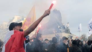 Supporters of the movement Generation Identity light up flares during a demonstration Saturday, Feb. 20, 2021 in Paris