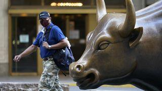 """Un homme passe devant le """"Charging Bull"""", à New York, le 8 septembre 2020"""