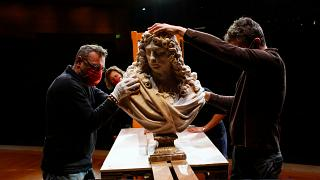 Workers handle a bust of Charles Le Brun by French sculptor Antoine Coysevox, in the Louvre museum