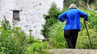 A lady walks in the countryside near her home.