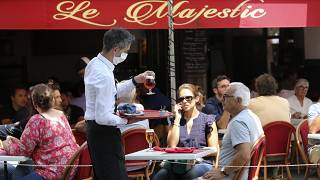 A bartender brings drinks to customers in a cafe of Saint Jean de Luz, southwestern France, Tuesday June 2, 2020.