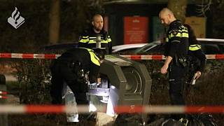 Dutch police inspect the waste container where the baby was found near Amsterdam.