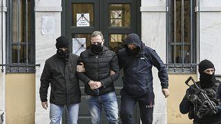 يغادر المدير الفني السابق للمسرح الوطني اليوناني ديميتريس ليجناديس (في الوسط)، برفقة ضباط الشرطة، مكتب قاضي التحقيق في أثينا.